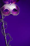 Purple Mardi-Gras or Venetian mask on purple background. A purple mardi gras mask on a purple background with beads. Carnivale costume