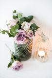 Purple, mauve color fresh summer roses in vase with white wall b Stock Photos
