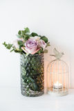 Purple, mauve color fresh summer roses in vase with white wall b Stock Images