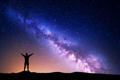 Purple Milky Way with silhouette of a standing man Stock Photos