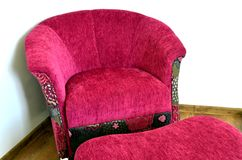 Purple modern chair. And ottoman on brown wooden floor Stock Photography