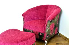 Purple modern chair. And ottoman on brown wooden floor Stock Image