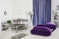 Purple modern living room. Purple armchair and grey rug in modern living room interior with metal table in front of a sofa with patterned pillows next to a lamp Stock Images