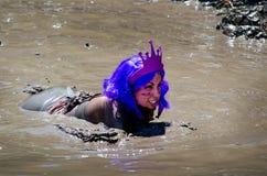 Purple mud princess. A woman in purple hair and a princess tiara swims in a muddy river at the 2012 mudathlon Royalty Free Stock Photo