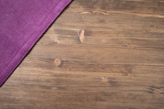 Purple  napkin from left top corner wooden table Royalty Free Stock Photography