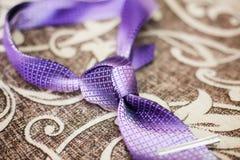 Purple necktie with trinity tie knot on a sofa, closeup. Purple necktie with trinity tie knot on a sofa, close-up Royalty Free Stock Photos