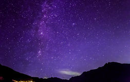 Purple night sky stars. Milky way across mountains Stock Image