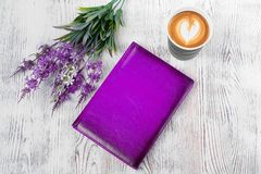 A purple notepad cup of coffee flowers. On a white wooden background Stock Photos