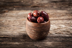 Purple organic olives. Purple olives on wooden table Royalty Free Stock Image