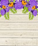 Purple and orange flowers on wooden background Stock Image