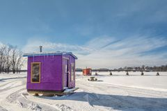 Purple and Orange Ice Fishing Cabins in Ste-Rose Laval. Ice Fishing cabins in a vast spaces on the frozen Rivière des Mille Îles in Ste-Rose, Laval, Quebec Royalty Free Stock Images
