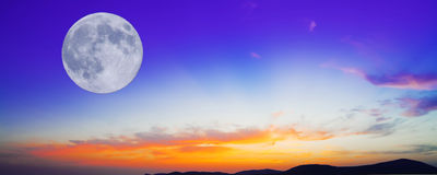 Purple and orange sunset with moon. Huge moon  in an orange and blue sunset Stock Image