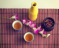 Purple orchid and black tea still life composition Stock Photos