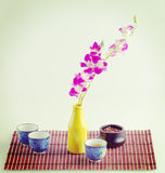 Purple orchid and black tea still life composition Royalty Free Stock Photography