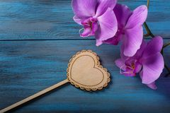 Purple Orchid and  heart. On blue, old wooden background Royalty Free Stock Photo