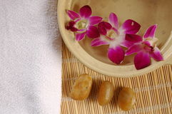 Purple orchid in perfumed water, white area for copy space. Therapy stones, towel, flowers and scented water, important elements in a spa Royalty Free Stock Photo