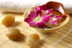 Purple orchid in a spa. Therapy stones, towel, flowers and scented water, important elements in a spa Royalty Free Stock Images