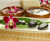 Purple orchid in the spa. Tropical spa set up with orchid, therapy stones, fern leaves, loofah and white towel Stock Photo