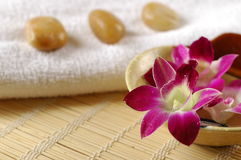Purple orchid, towel and therapy stone. Therapy stones, towel, flowers and scented water, important elements in a spa Stock Photo