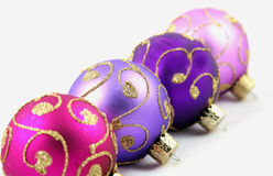 Purple Ornaments. Christmas ornaments with gold glitter detail against white background royalty free stock photo