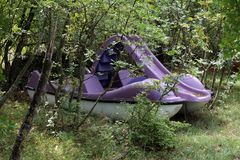 Purple paddle boat with plastic steps and slide in middle taken out of water and left in backyard surrounded with uncut grass and. Trees on warm sunny day stock images