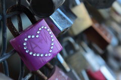 Purple padlock with heart. Attached to the rail with other padlocks Stock Photos