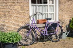 Purple ladies bike against a brick wall. Purple painted ladies bike against an old brick wall in the Netherlands. It is a sunny day in the spring season Stock Photo