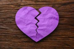 Purple Paper broken heart with on wooden Stock Image