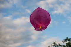 Purple sky lantern flying away into the sky stock photo