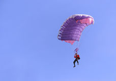 Purple parachute. A purple parachute in a blue sky on a sunny day Royalty Free Stock Photography