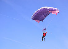 Purple parachute. A purple parachute in a blue sky on a sunny day Royalty Free Stock Images
