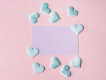 Purple pastel card and hearts on pink textured background Stock Images