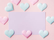 Purple pastel card and hearts on pink textured background. Pastel color card on pink textured background. Baby birthday party invitation or valentine with green royalty free stock image
