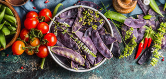 Purple pea pods in metal bowl with tomatoes and cooking ingredients, top view. Royalty Free Stock Photography