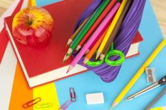 Pencil case and an apple on top of a red book. Purple pencil case full of colouring pencils and a red apple on top of a red book on a busy desk Royalty Free Stock Photography