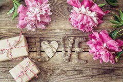 Purple peonies with letters LOVE and gift boxes on old wooden bo Royalty Free Stock Photos