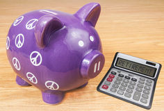 Purple Piggy bank with calculator Royalty Free Stock Photos