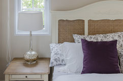Purple pillow on wooden bed  with lamp in bedroom Royalty Free Stock Photography