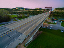 Purple and Pink Angled Aerial Pennybacker Bridge at sunset with cars showing motion from Long Exposure taken by Drone Royalty Free Stock Image