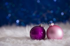 Purple and pink Christmas balls on white fur with garland lights. Two Christmas balls on white fur with garland lights on blue bokeh background. New year card Royalty Free Stock Image