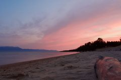 Purple and pink sunrise over the Baikal lake. Scenic purple and pink sunrise over the Baikal lake and tree trunk in the foreground, Russia royalty free stock image