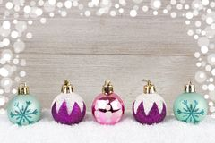 Purple, pink and turquoise Christmas baubles in snow against wood Stock Photo