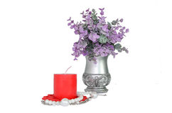 Purple plant with vase plant and red candle. Plant in antique-style Decorative silver vase with red candle and a pearl bracelet Stock Photo