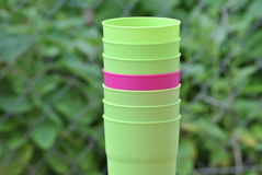 Purple plastic cup between green ones. A purple plastic cup in between green with a blurred background royalty free stock photos