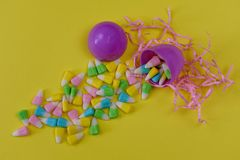 Purple plastic Easter egg spilling candy on a yellow background royalty free stock photography