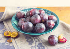 Purple plums in a green plate Stock Photos