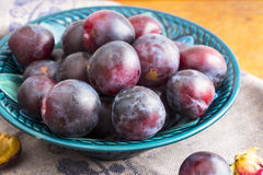 Purple plums in a green plate Stock Photography