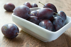 Purple plums in a white bowl on wooden table background Stock Photo