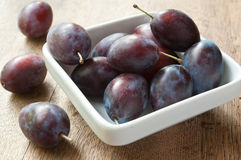 Purple plums in a white bowl on wooden table background Royalty Free Stock Photos
