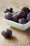 Purple plums in a white bowl on wooden table background Stock Images